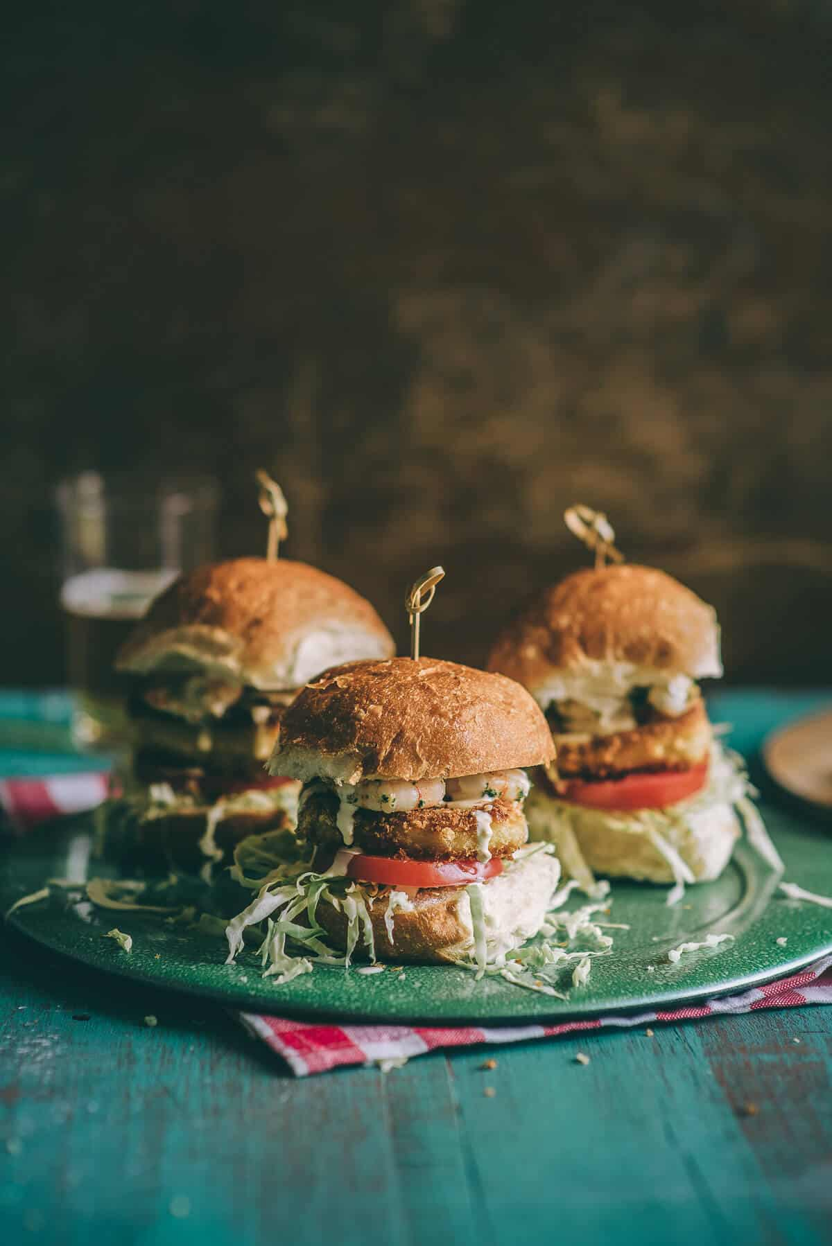 three burgers on a green plate on a table