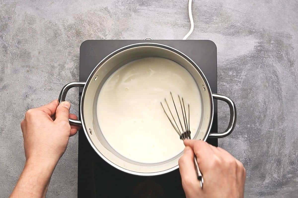 whisking milk in a pot on a hot plate