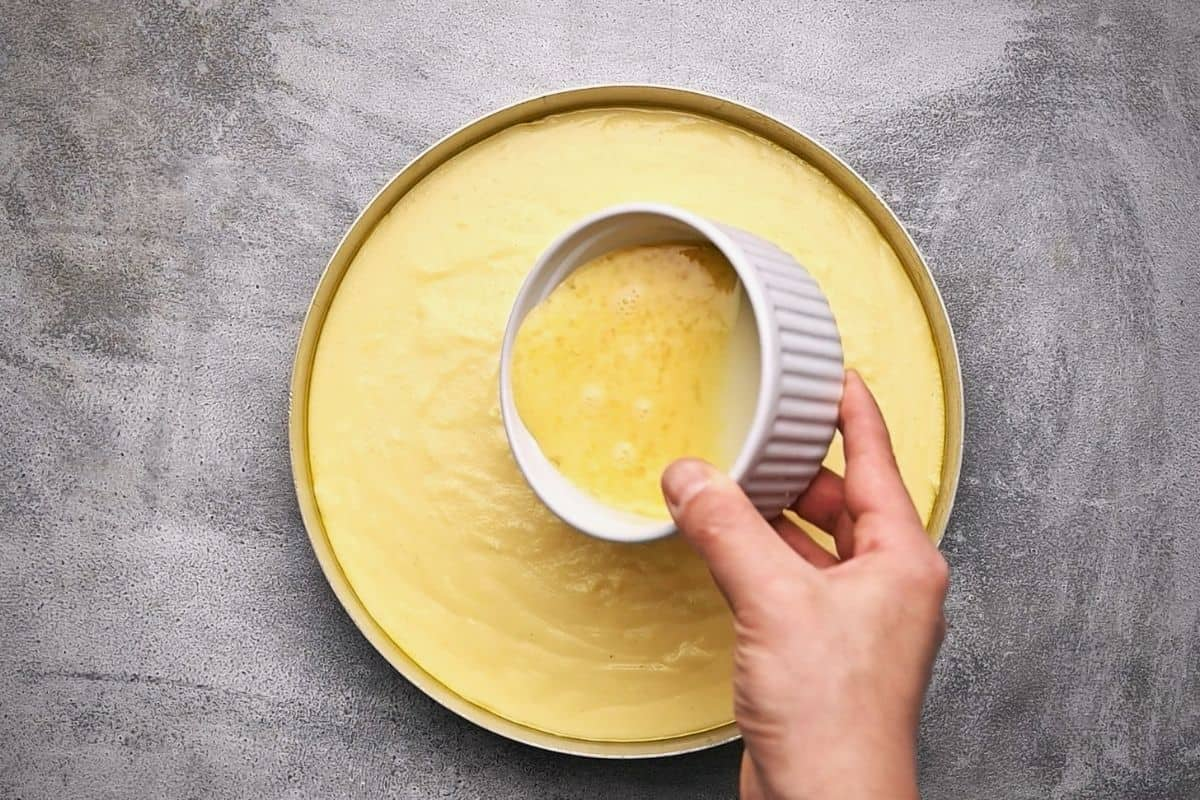 pouring beaten eggs from a ramekin onto an uncooked pie in a round baking dish