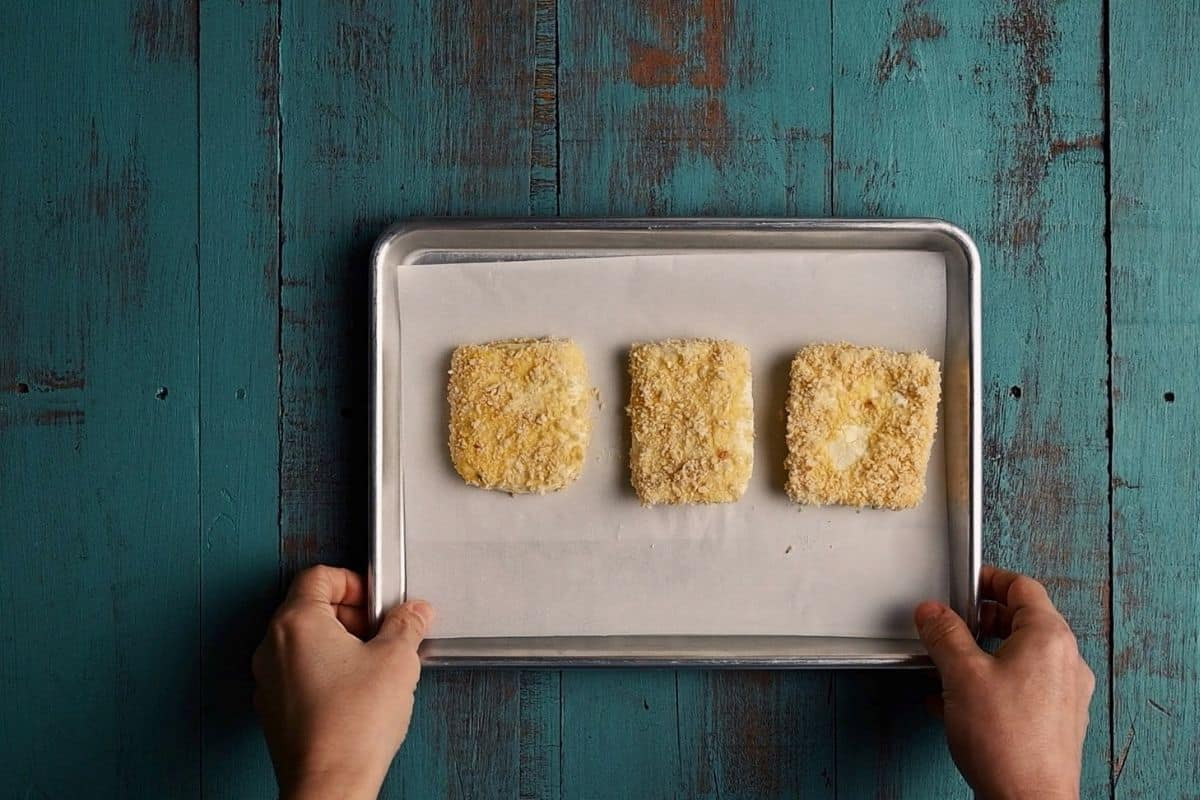 crumbed cheese on a tray being held by two hands