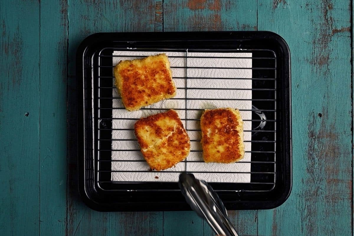 crumbed and fried halloumi cheese on a rack