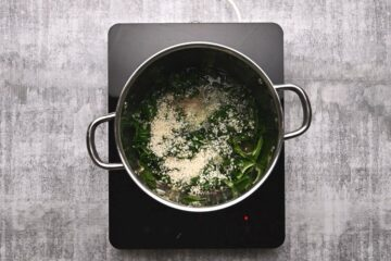 spinach and rice being cooked in a pot