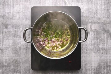 onions frying in olive oil in a pot