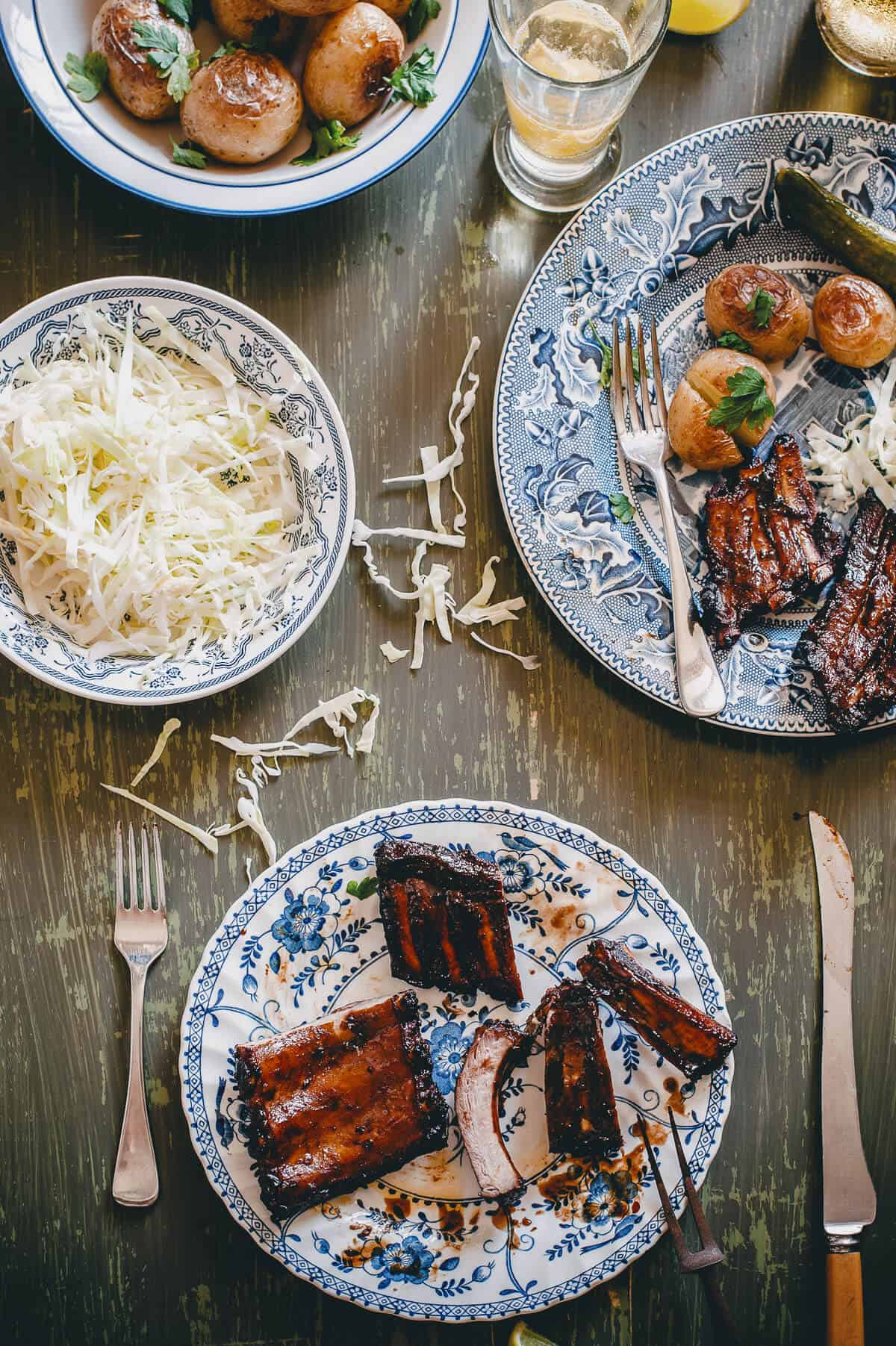 a table with cooked ribs coleslaw and baked potatoes