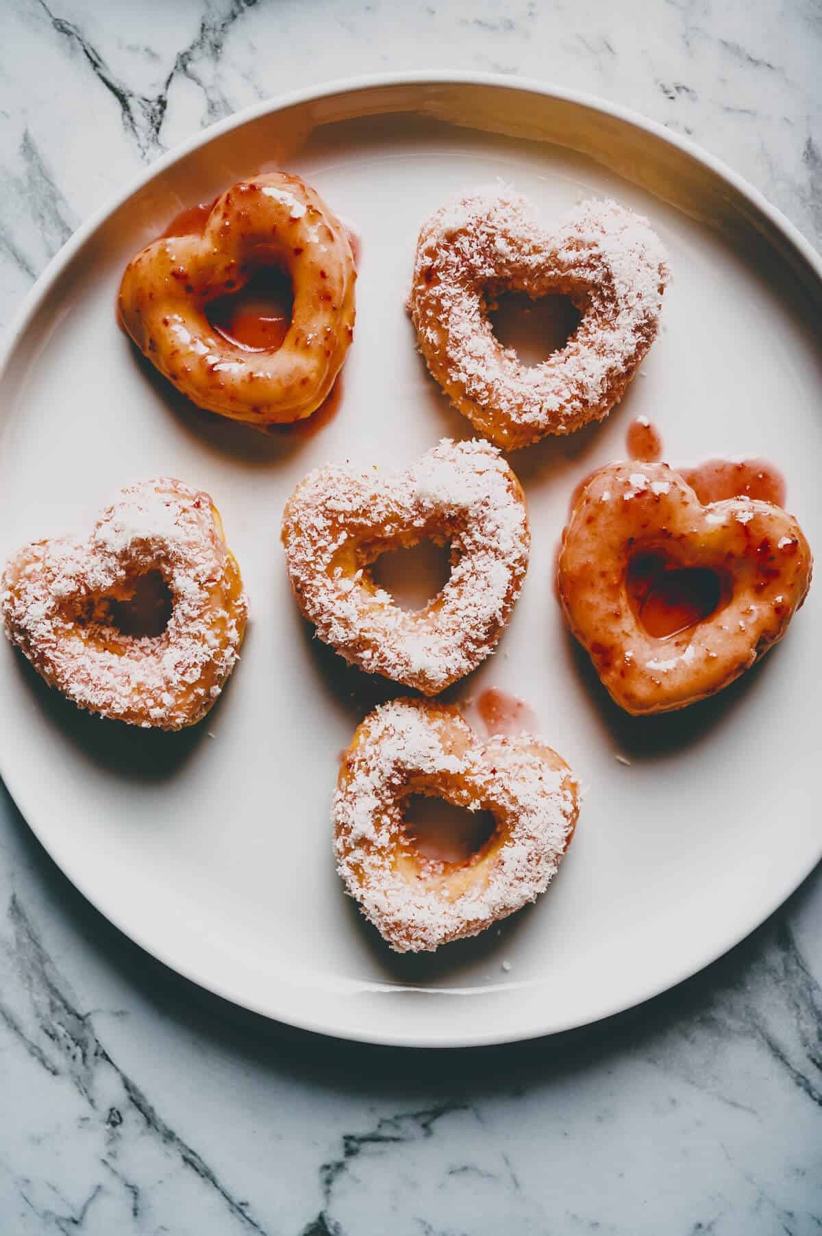 heart shaped doughnuts served on a white plate