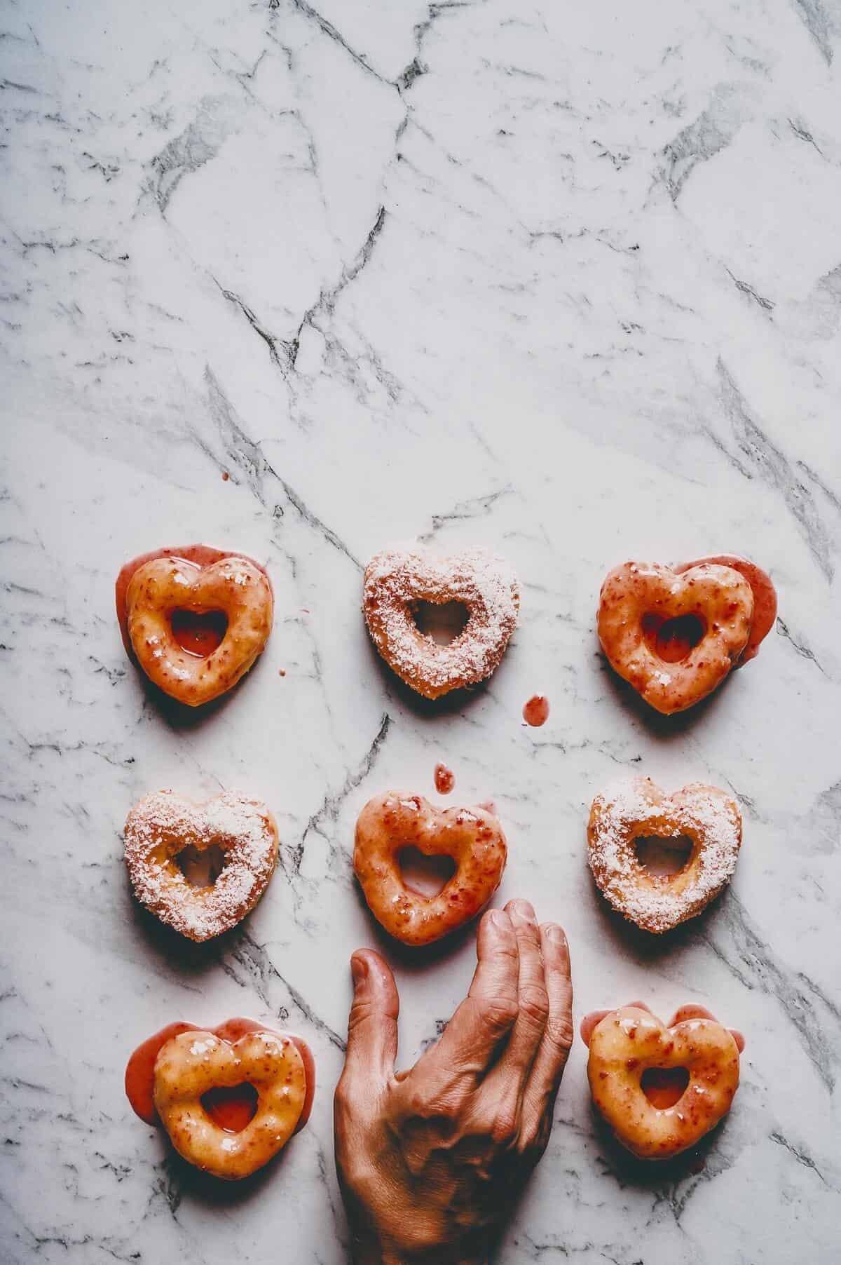 a hand reaching to grab a heart shaped doughnut
