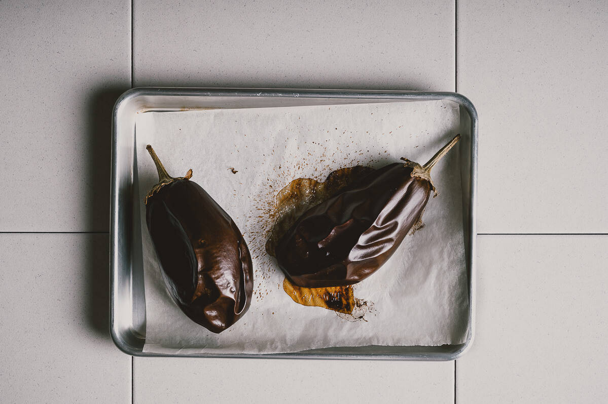 two roasted eggplants on a lined baking tray