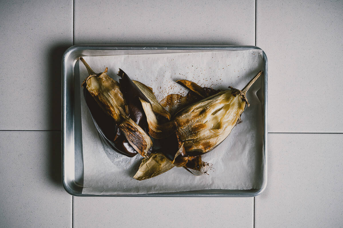 two roasted eggplants with their skin peeled on a baking tray