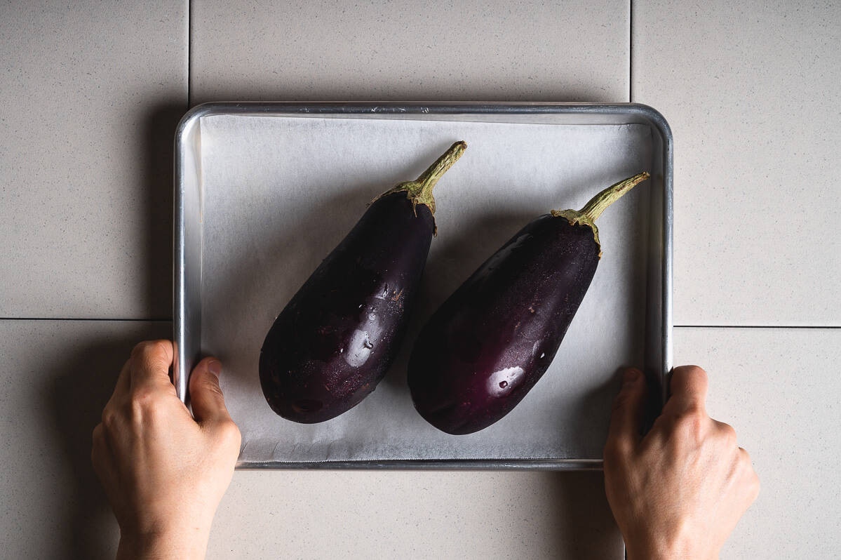two hands holding a baking tray with 2 eggplants on it
