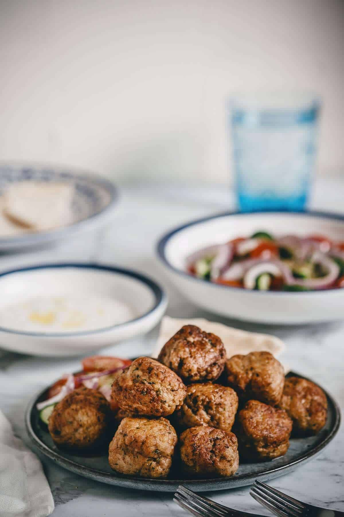 a plate of Greek meatballs with tzatziki and Greek salad in the background
