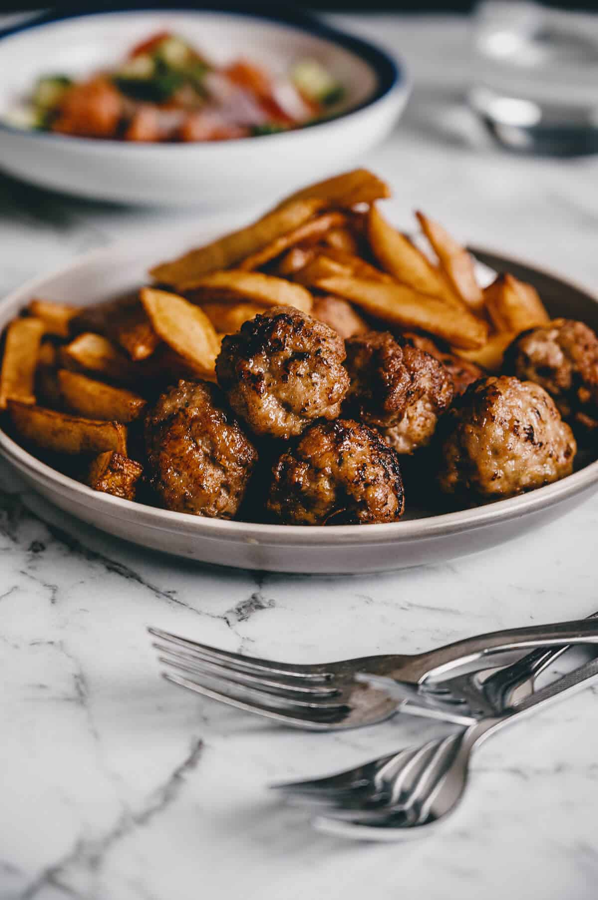 close up of fried meatballs with french fries in the background