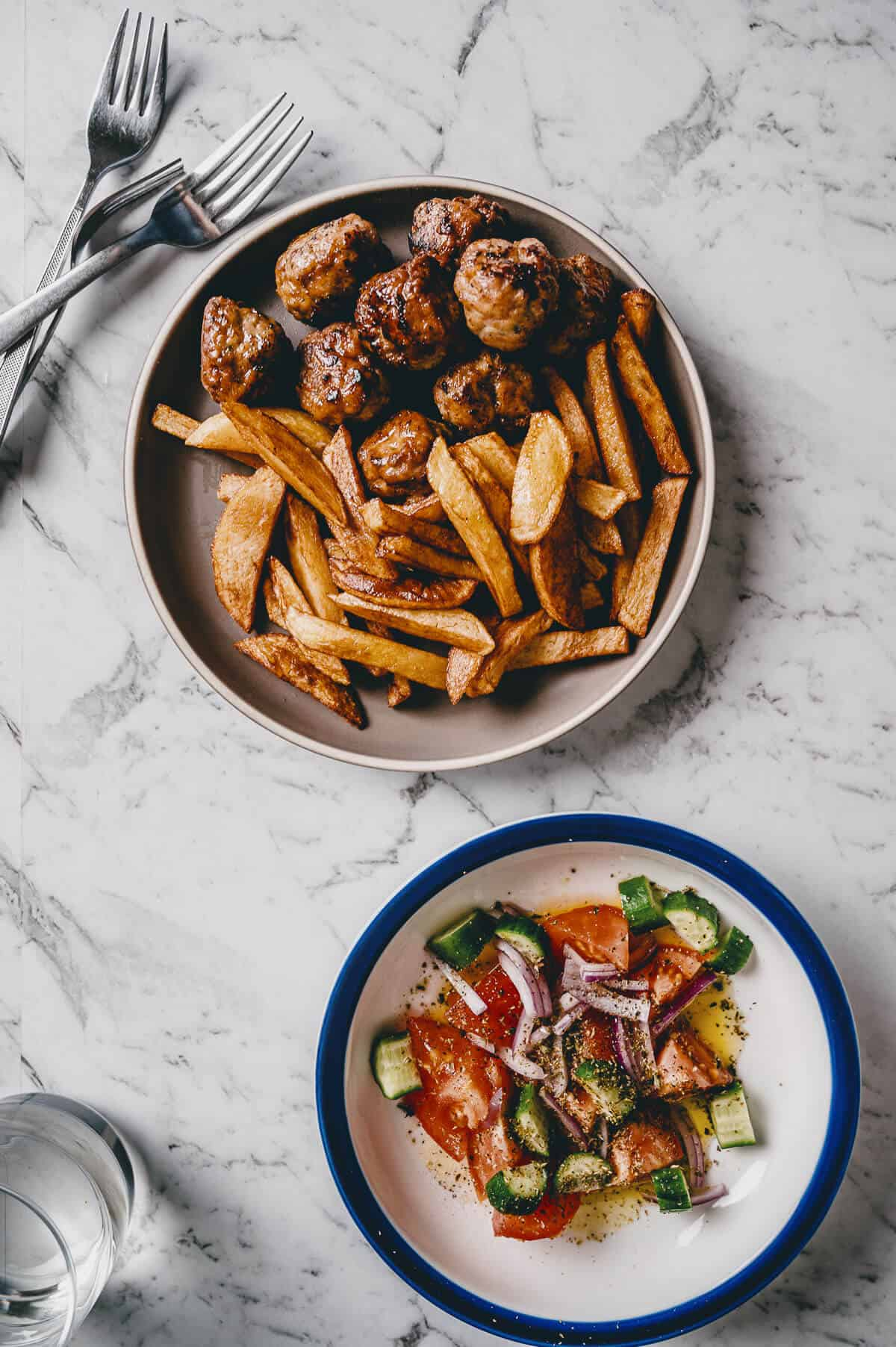 a plate filled with cooked meatballs and fries and a bowl of salad