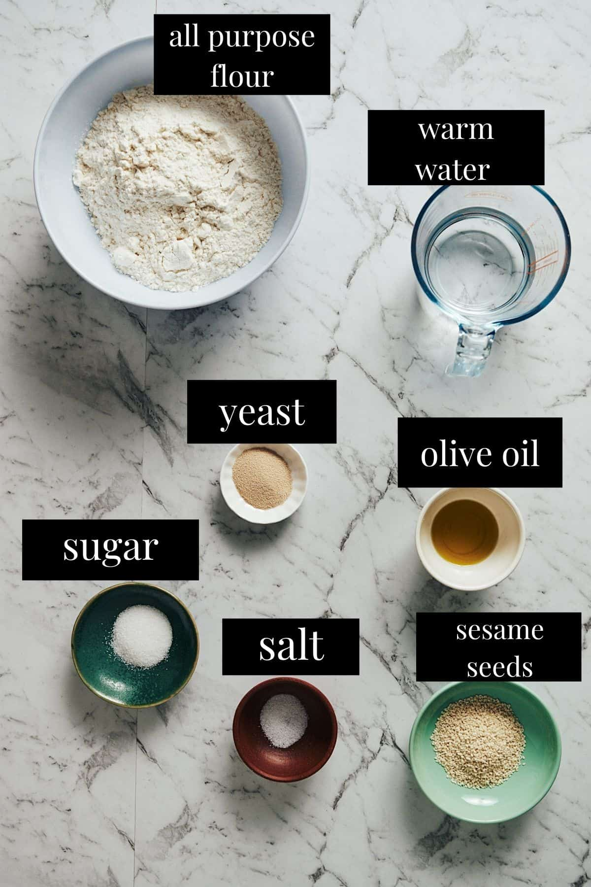 labeled ingredients laid out on a table to make greek lagana bread