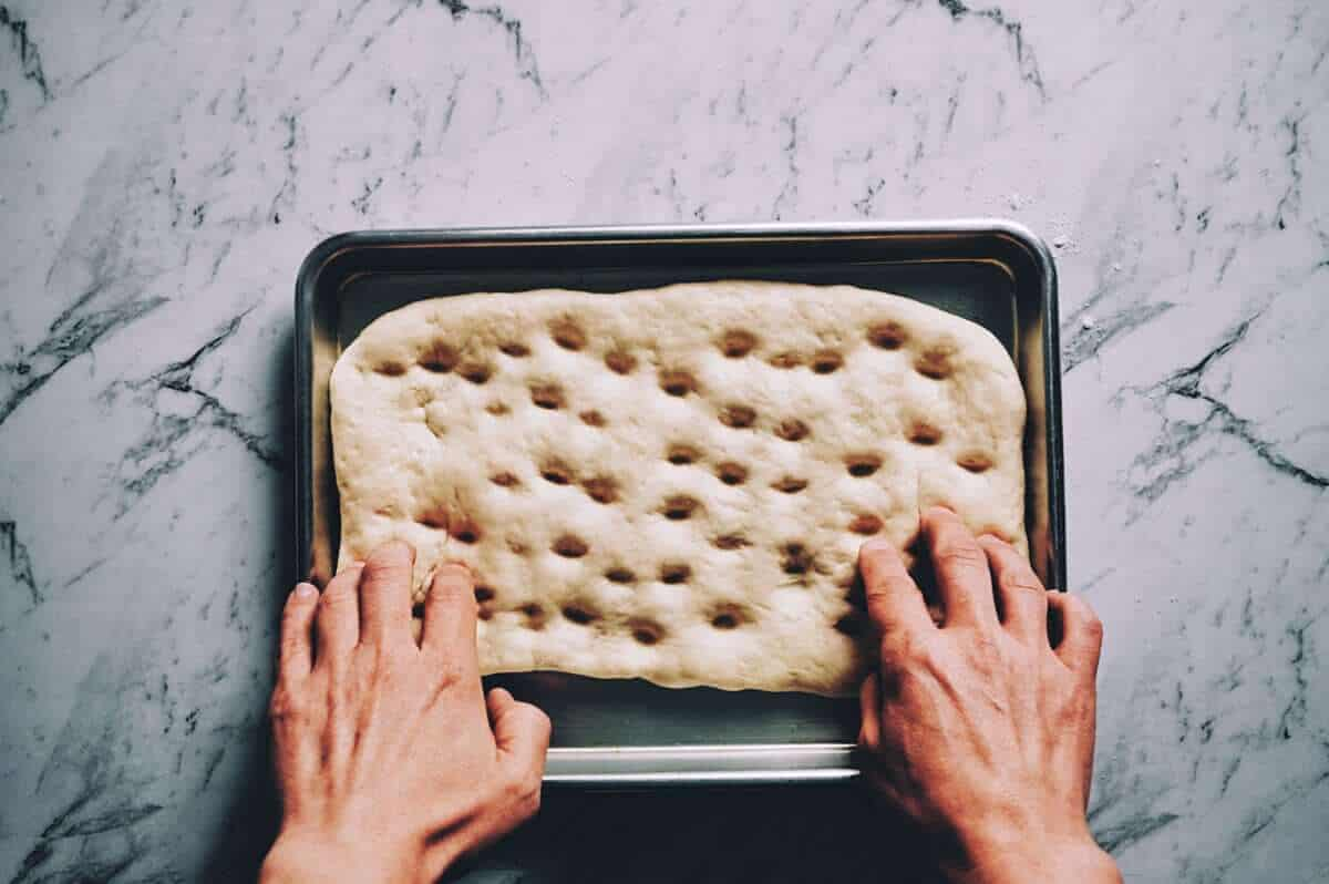 two hands making dimples in a shaped dough in a baking tray