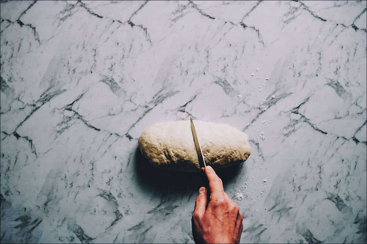 cutting dough in half with a knife