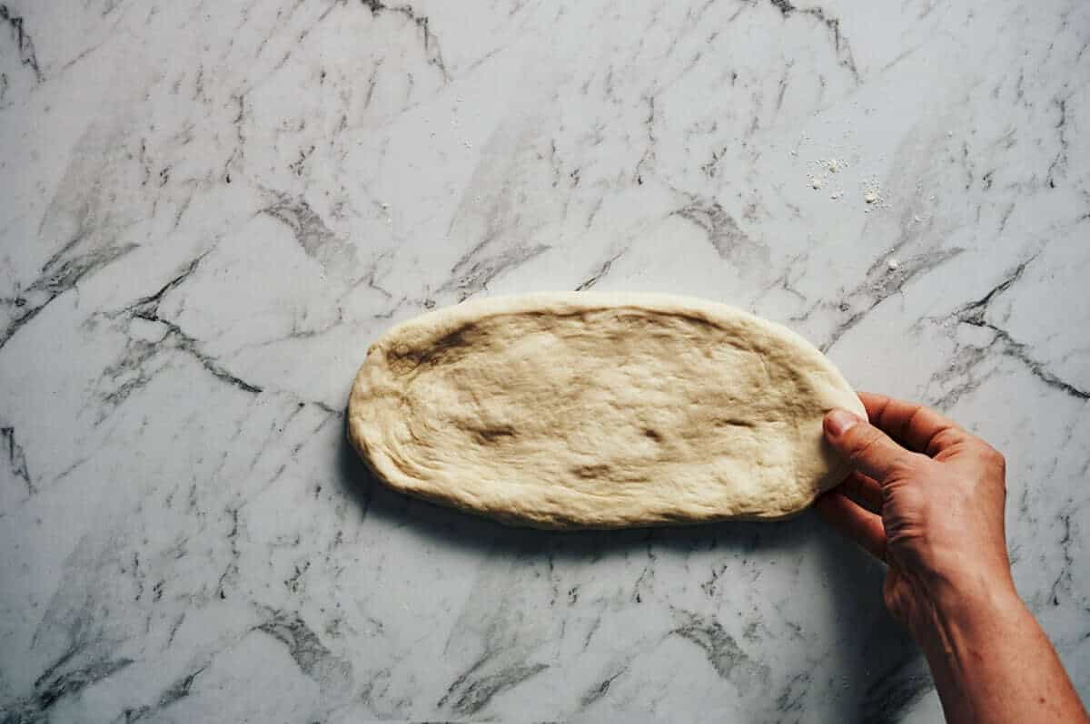 shaping a greek flatbread with a hand