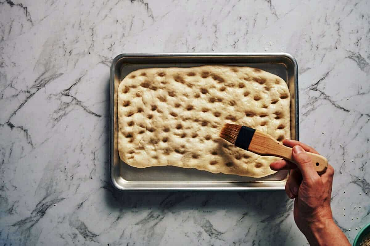 brushing olive oil over a flatbread before it gets baked
