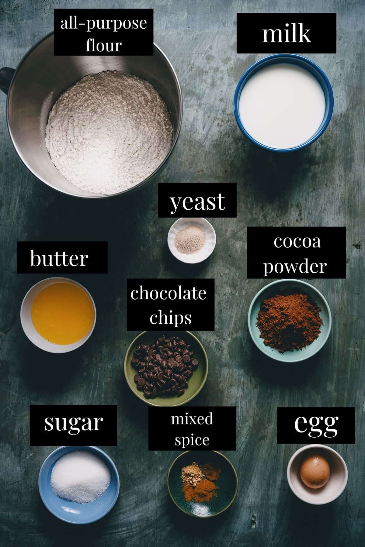 bowls of ingredients used to make chocolate hot cross buns on a dark background