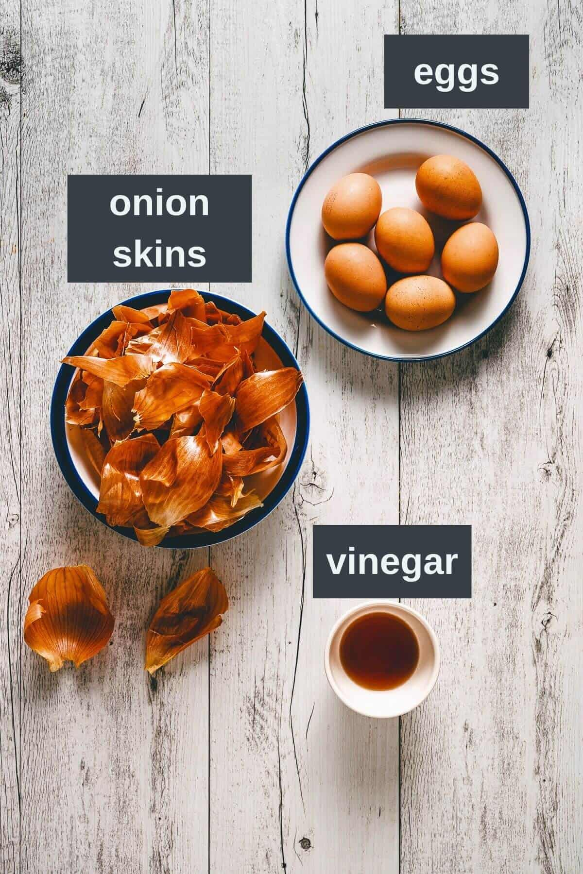 a white wooden table with a bowl filled with uncooked eggs, a bowl of onion skins and small bowl of vinegar