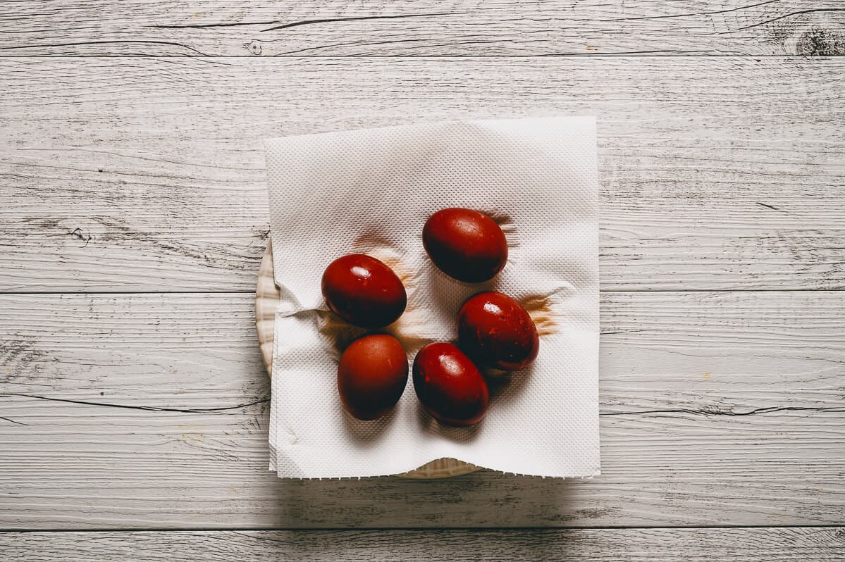 five red eggs on a paper towel lined plate