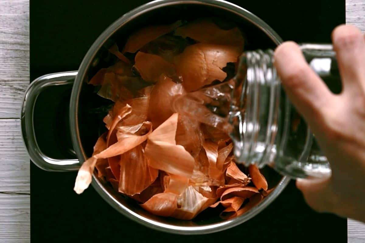 pouring water into a pot with onion skins
