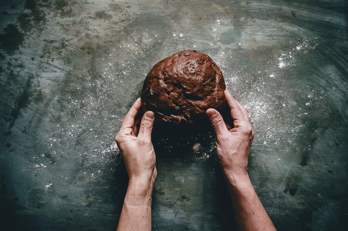 a pair of hands handling chocolate dough