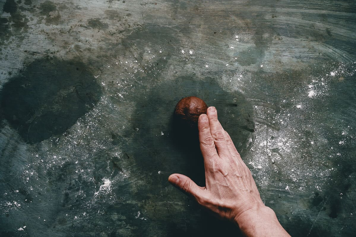 a hand rolling chocolate dough into a ball on a dark surface