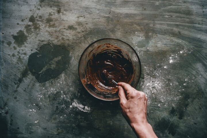 chocolate sauce being whisked in a glass bowl