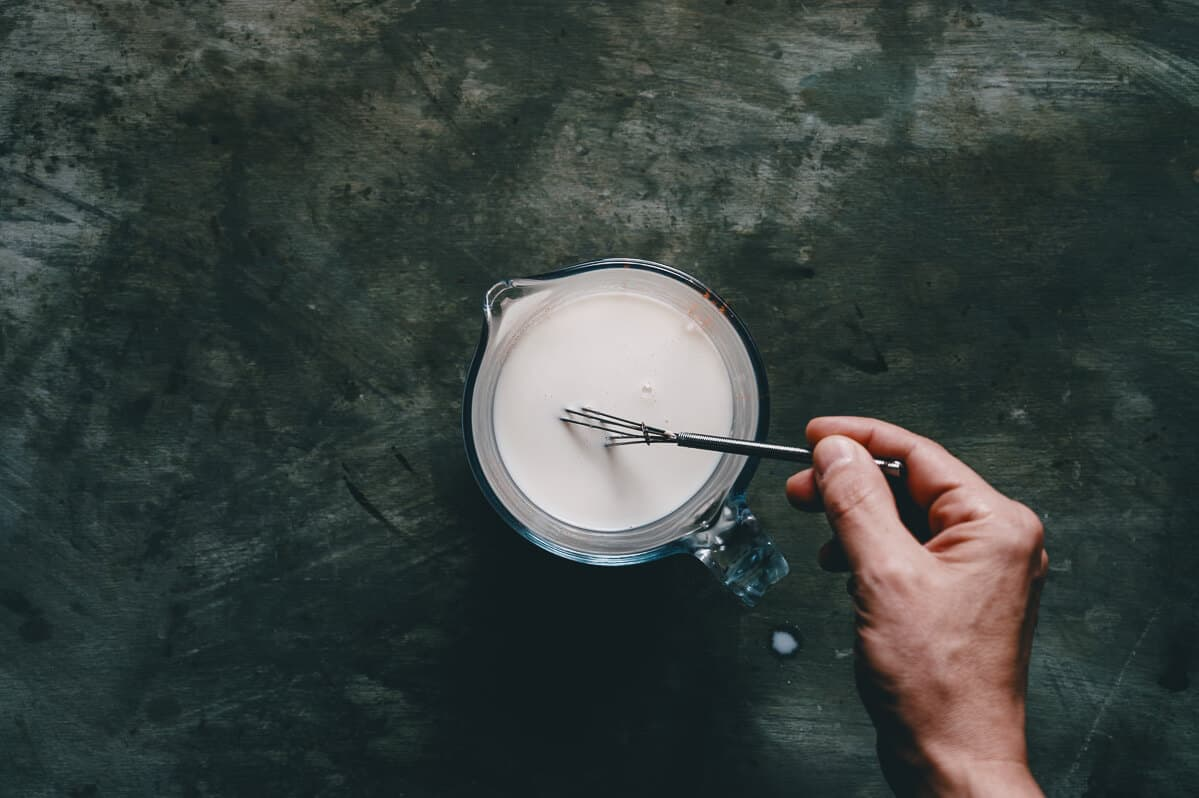 milk being whisked in a jug on a dark surface