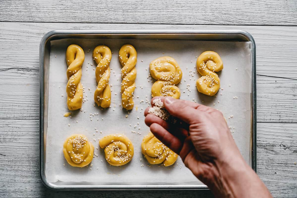 sprinkling sesame seeds over cookies
