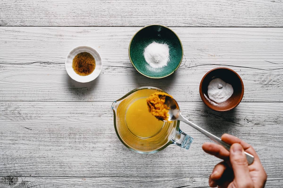 orange zest being spooned into a jug with orange juice