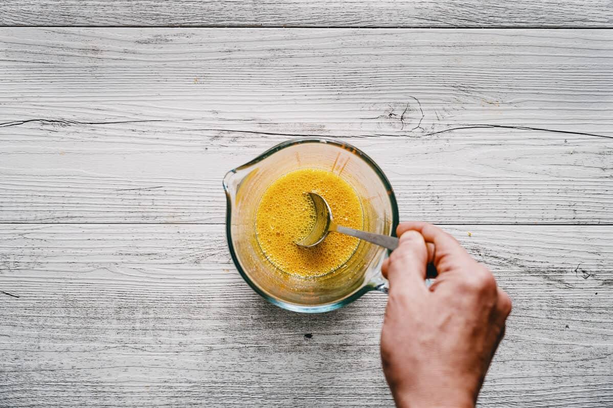 a spoon stirring orange juice in a jug