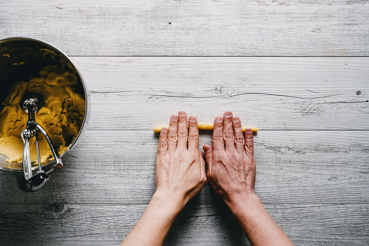two hands rolling out cooking dough on a white table