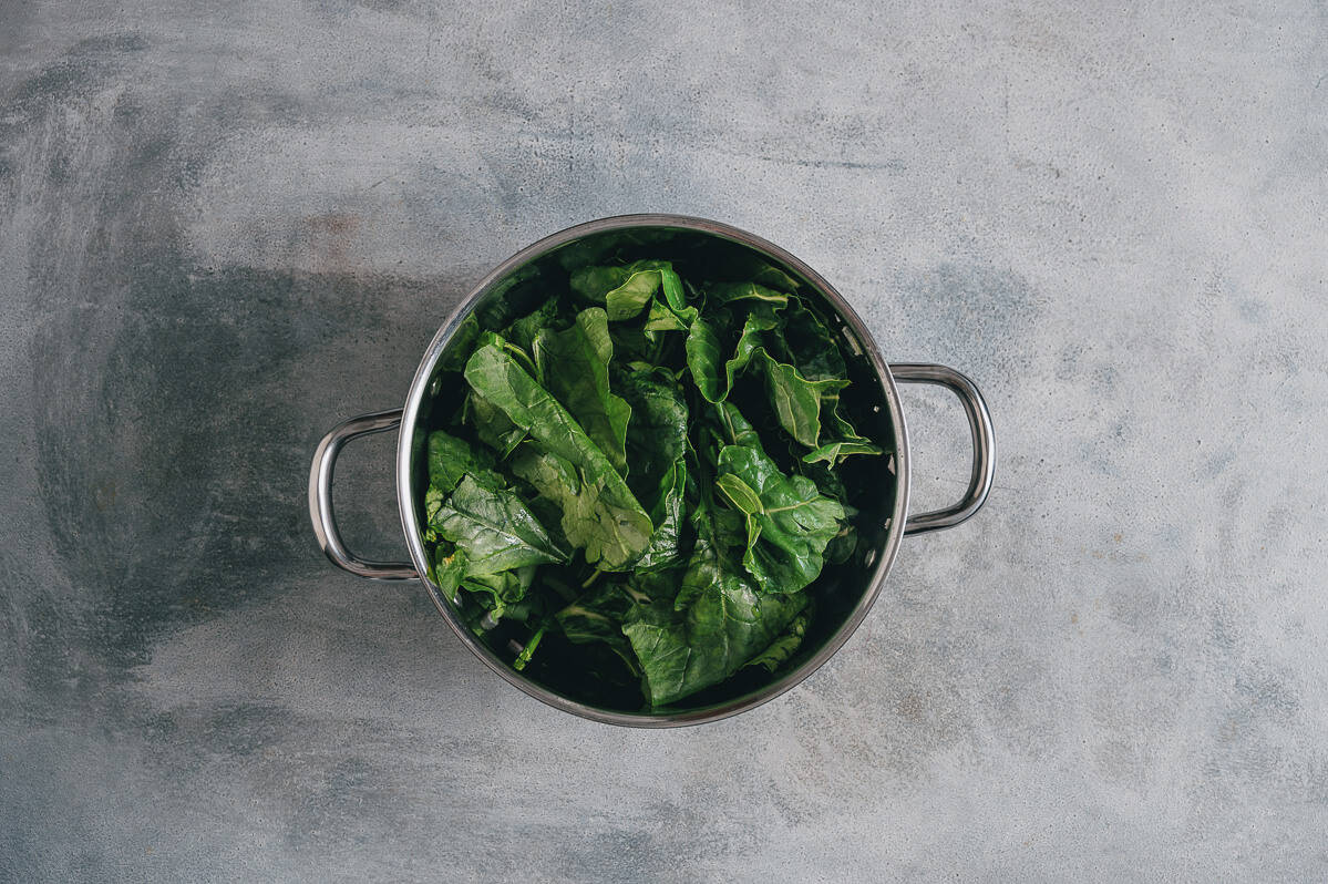 a pot filled with spinach leaves.