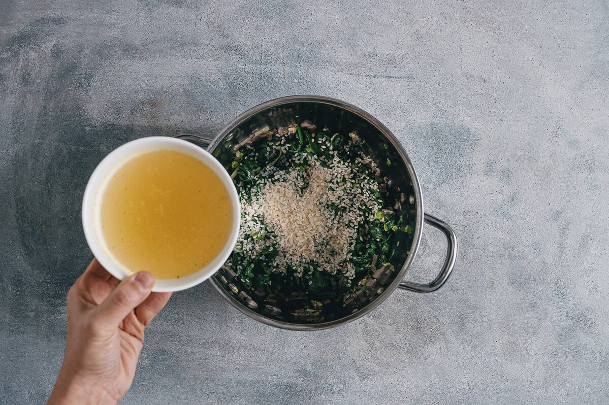 pouring chicken stock into a pot filled with spinach and rice.