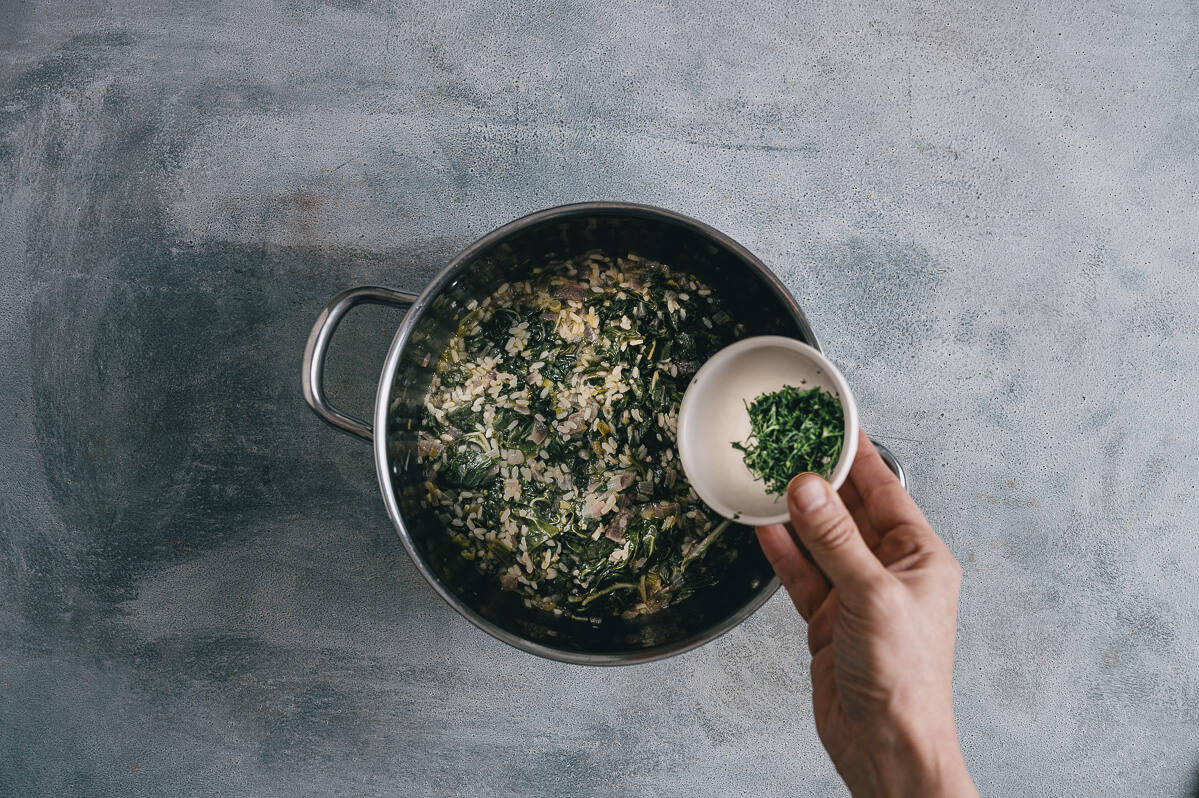 adding herbs to a pot filled with cooked spinach and rice.