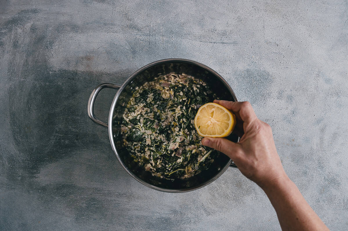 squeezing lemon into a pot filled with cooked spinach and rice.