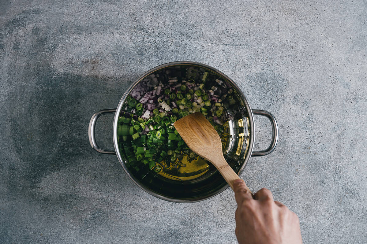 sautéing green and red onions in olive oil in a pot.