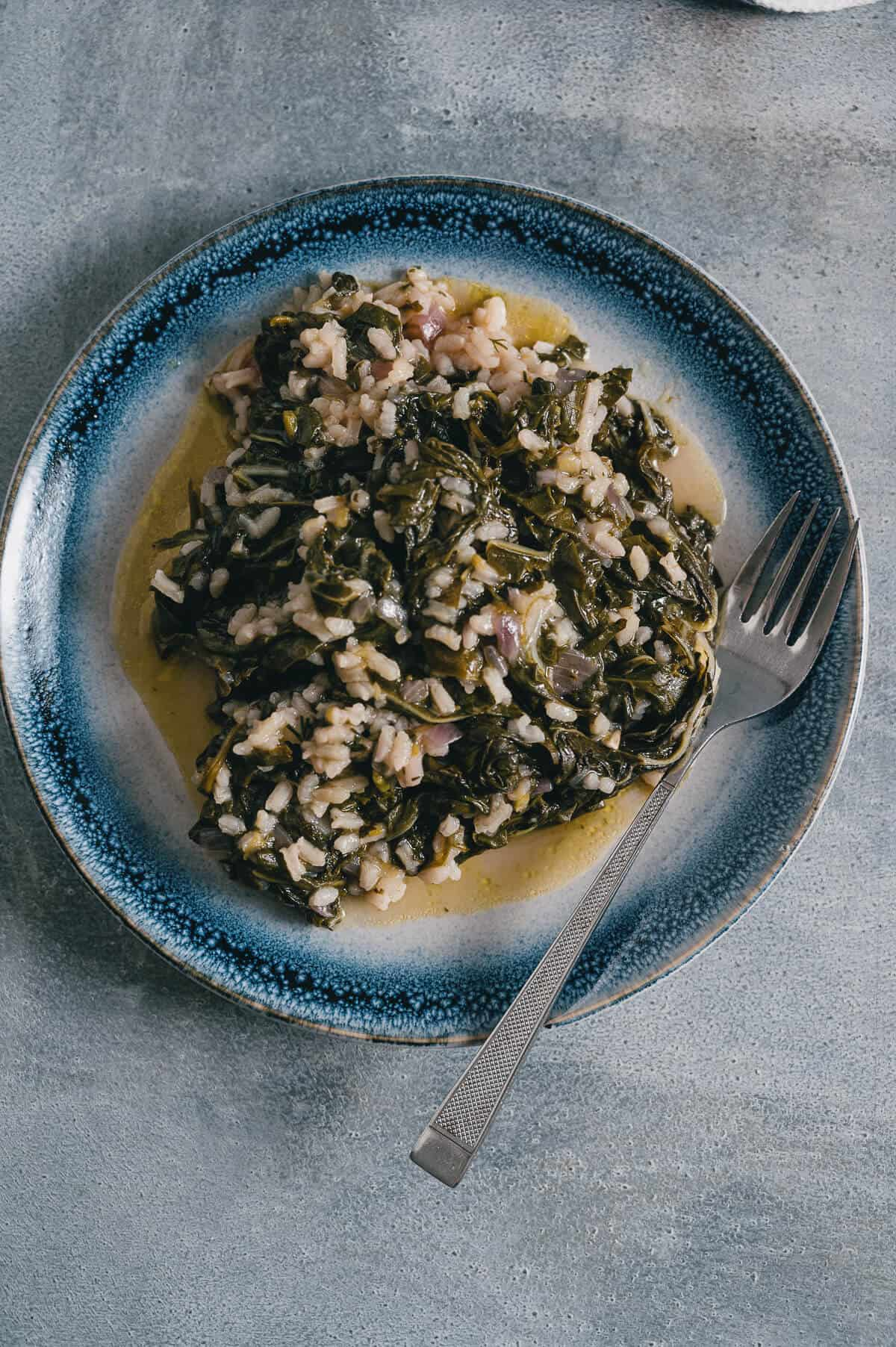 a plate filled with cooked spinach and rice known as spanakorizo.