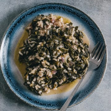 a blue and white late filled with a greek spinach and rice dish known as spanakorizo.