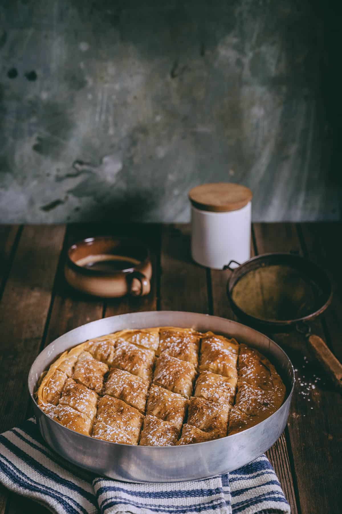 Greek pumpkin pie served in a baking dish on a wooden table.