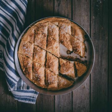 a greek pie made with filo and dusted with cinnamon and powdered sugar.