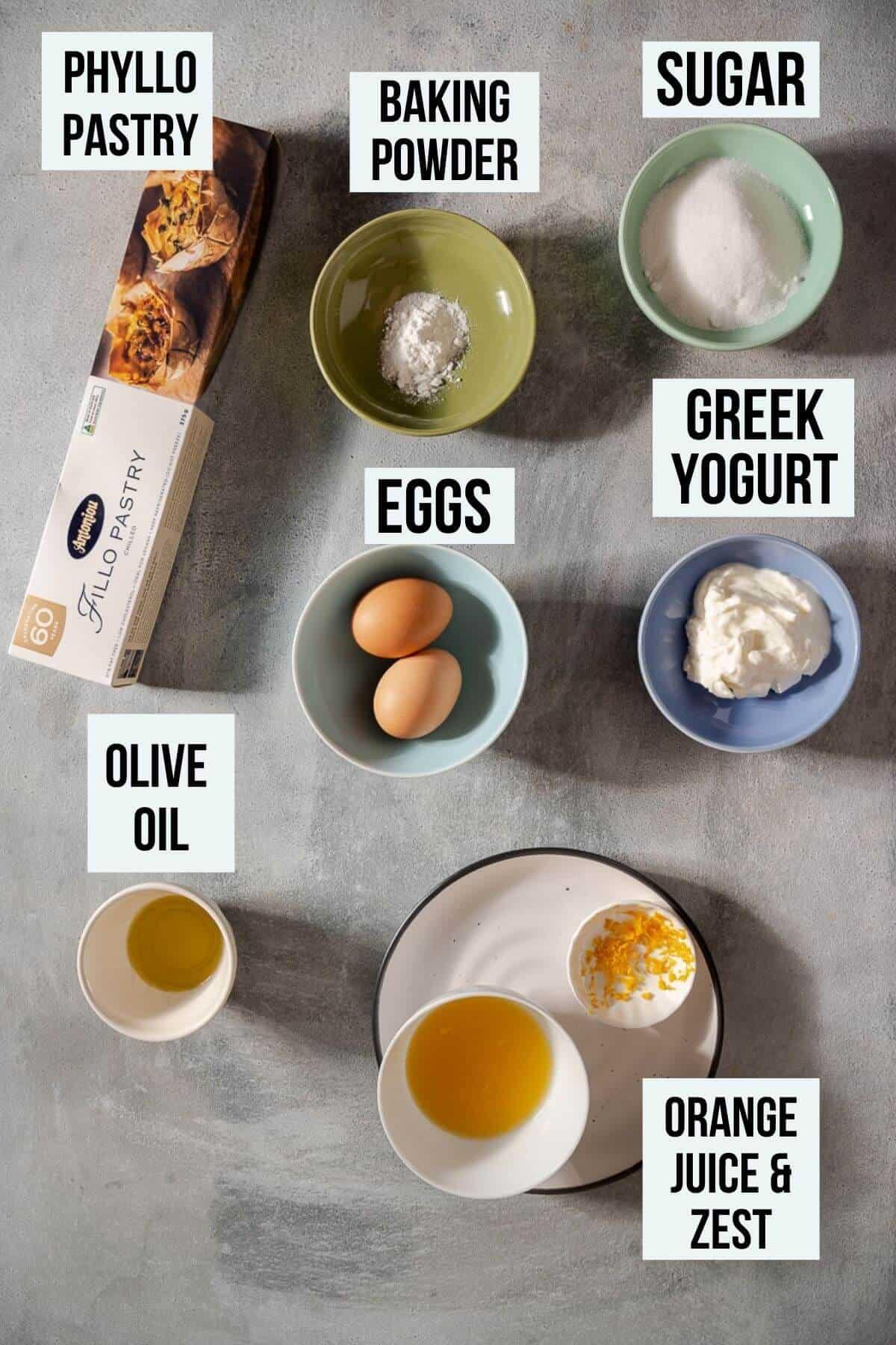 labelled ingredients on a grey table to make portokalopita.