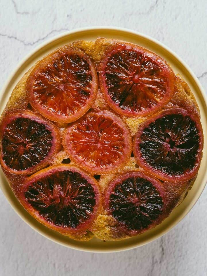 a to[p down view of a blood orange cake on a cake stand.