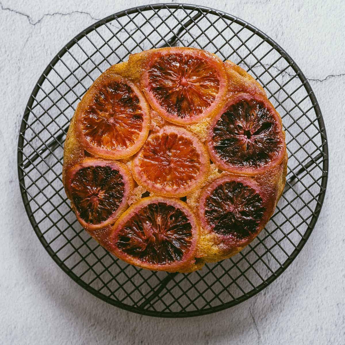 a blood orange cake on a cooling rack.